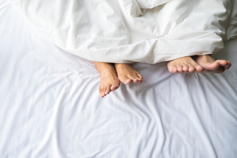 pareja acostada en la cama con nórdico